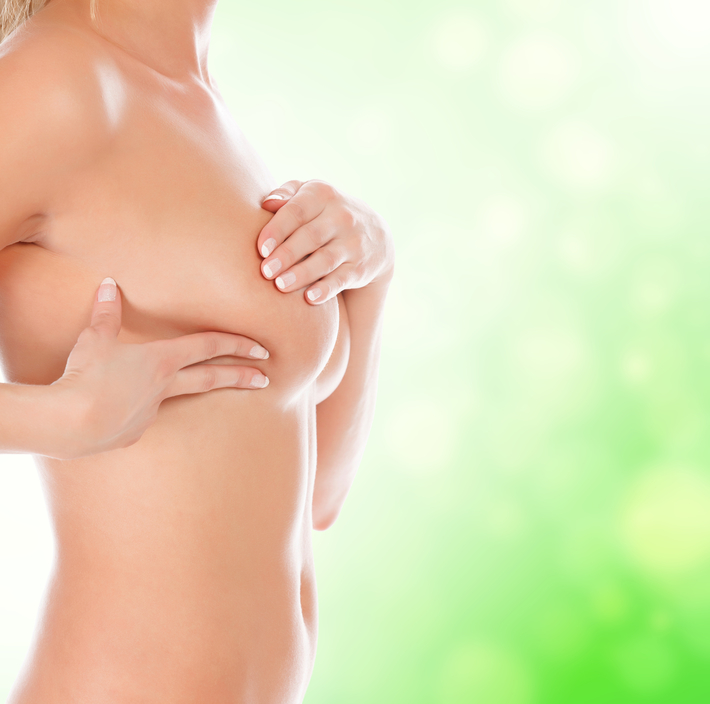 Woman controlling breast for cancer, green blurred background
